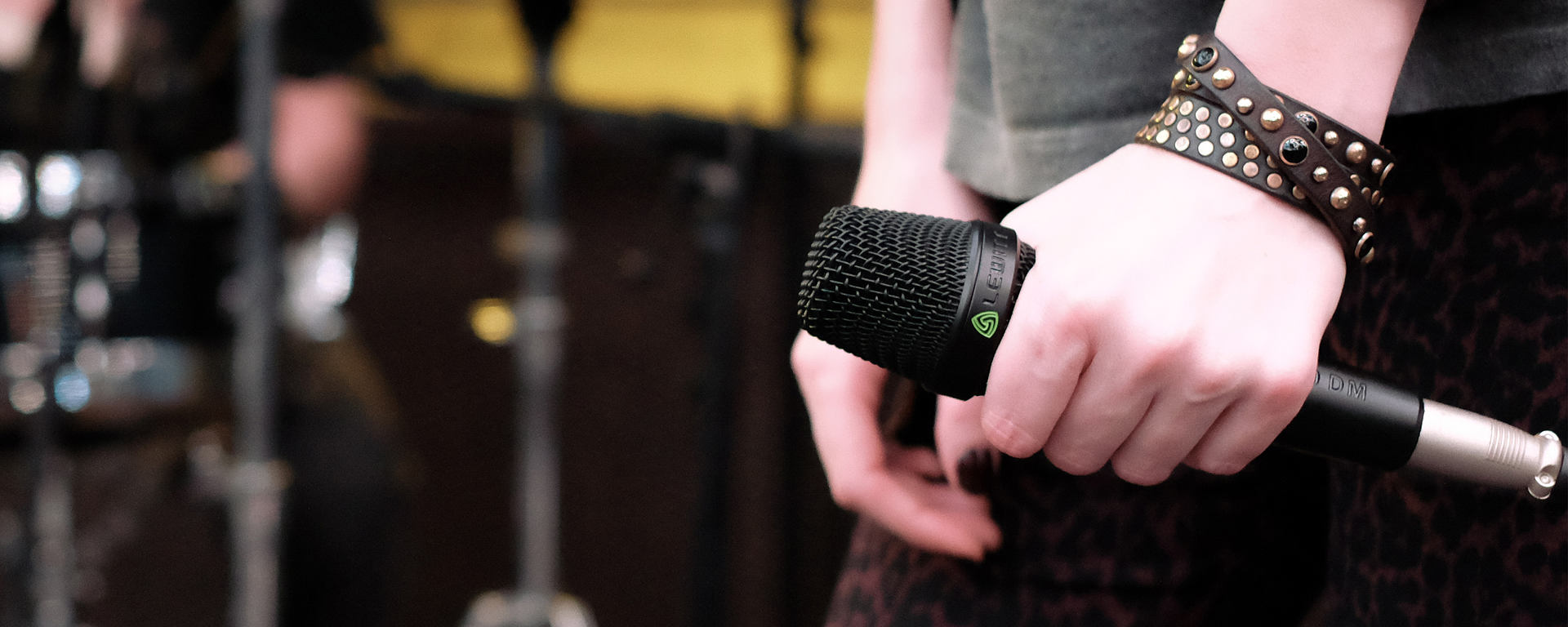 A woman's hand holding an MTP 940 microphone on stage